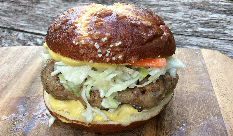 Bratwurst Burger with Cabbage Slaw and Spicy Horseradish Mustard on a Pretzel Bun